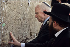 Sen. John McCain touches the stones Wednesday of the Western Wall, Judaism's holiest site, in Jerusalem's Old City, while bystanders clapped and cheered. The senator also placed a prayer between the cracks.