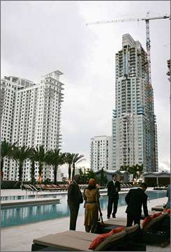 "People stand pool-side during the inauguration of a new building owned by billionaire U.S. condo builder Jorge Perez in downtown Miami in October 2007. But Florida population ""growth stopped on a dime"" in the past year, says Brookings Institute demographer William Frey."