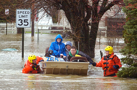 Henderson County Rescue Squad members Scott Trodglen, left, and Amanda Coghill evacuate Katie Rheinhardt, Amy Thomas, Andrew Rheinhardt and their two year-old daughter Reed from their flooded home in Henderson, Ky., March 19. Flood and flash flood warnings are still out for many parts of the Midwest.