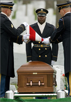 Killed in Iraq: A U.S. Army Honor Guard casket team folds a U.S. flag over the casket of Army Cpl. Luke Runyan during funeral services at Arlington National Cemetery in Virginia on March 10.