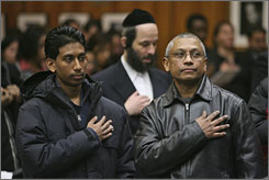 Army Sgt. Feyad Mohammed's father Fazal, right, and brother Fadeel, left, pledge allegiance during Feyad's oath of citizenship ceremony in New York, in January. U.S. Citizenship and Immigration Services officials are working weekends to cut down the backlog of citizenship applications that have piled up since last summer.