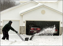 Frank Smith clears his driveway in Beach Park, Ill. Friday afternoon.