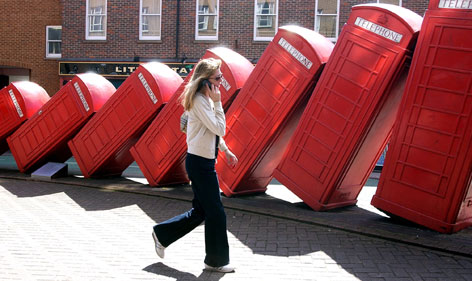 A pedestrian speaking on a mobile phone walks past a series of old red British phone boxes modeled into a work of art in Kingston town centre, southwest of London April 22, 2004. Only 12,700 of the iconic booths remain on British streets.