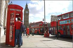 Tourists in London's Parliament Square use a British Telecom red phone box on April 22, 2004. With many put out of commission by growing cellphone use, old ones can fetch $5,000 to $10,000 or more, depending on the make, year and condition.
