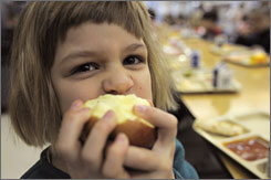 First-grader Jeanne Grutchfield munches on an apple at Fisher Hill School in Orange, Mass., a school that's joined a growing movement to supply cafeterias with fresh produce and support local growers at the same time.