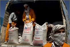 Afghan workers deliver bags of wheat in Kabul during a World Food Program distribution event March 13. The price of wheat flour, the staple food of Afghans, has increased by approximately 58% since January 2007.