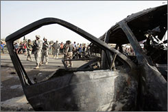 U.S. and Iraqi soldiers secure the site of a car bomb in Baghdad's Al-Shuala neighborhood on Sunday.