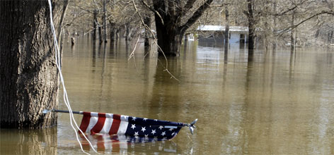 An American flag is covered by flood waters in a rural neighborhood outside of Des Arc, Ark. The White River flooded low-lying areas of Des Arc on Monday and have continued to rise, as other towns along the river were warned they could suffer their worst flooding in more than a quarter-century.