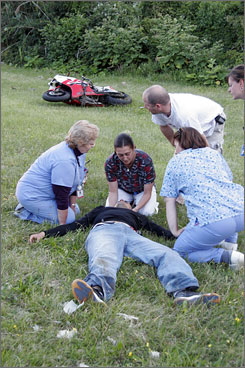 Abigail Barton, a registered nurse at Westchester Medical Center in Valhalla, N.Y., steadies a motorcycle rider's head after he was involved in an accident on the Taconic Parkway on July 31, 2007 near Ossining, N.Y. The driver lost control on a curve and his bike flipped a number of times.