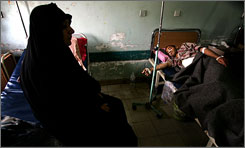 At a run-down hospital in Sadr City, Baghdad's Shiite-controlled slum, an Iraqi woman watches over a relative injured in recent clashes between Mahdi Army militia members and Iraqi forces.