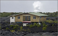 The home of Big Island resident Jean Olson sits atop of an active lava field, with volcanic gas billowing in the background on March 19 in Kalapana, Hawaii. Olson's home is built atop the 1990 lava flow which destroyed the town of Kalapana.