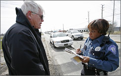 Indianapolis Metropolitan Police Department Public Safety Officer Clara Washington, right, takes the statement of Steve Slate who witnessed a traffic accident.