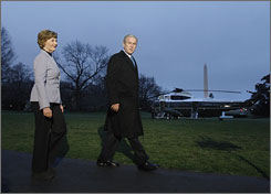 President Bush and first lady Laura Bush walk onto the South Lawn as Marine One waits to take off from the White House. Bush left for a week-long trip to Europe on Monday.