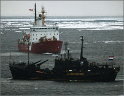 A Canadian coast guard icebreaker (top) keeps watch on the Sea Shepherd Conservation Society vessel Farley Mowat off the coast of Cape Breton island on Sunday.