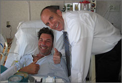 Jared Hjelmstad, right, of Temecula, Calif., visits with Garth Goodall at Rancho Springs Medical Center in Murrieta, Calif., on Feb. 27, days after Goodall collapsed while working out at a health club. Hjelmstad used hands-only CPR to keep Goodall's blood circulating until paramedics arrived and took over.