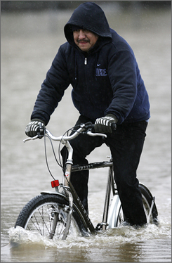 Miguel Cabrera rides his bicycle through a flooded street on Dec. 3 in Portland, Ore. A new American Public Health Association report says that in one potential connection between global warming and public health, the northwest could see heavy rainfall that may lead to flooding and overflow of sewage systems. That would cause an increase in the spread of disease.