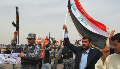 An Iraqi man carries an Iraqi flag beside a police commando during a rally in support of Prime Minister Nouri al-Maliki in the southern city of Basra, on Monday.
