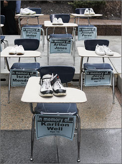 Shoes placed atop school desks are part of a memorial to 20 Chicago Public School students killed by gunfire since last September, displayed at a rally in downtown Chicago April 1.