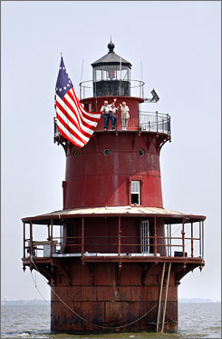 Dan and Jackie Billingsley, left, of Annapolis, Md., along with Elaine Klossner, of Manassas, Va., wave from the Newport News Middle Ground Lighthouse near the mouth of the James River in Virginia.