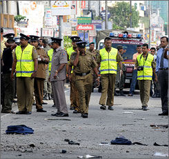 Sri Lankan security officials conduct investigations at the site of an improvised explosive device blast in Colombo on March 10. A new report indicates that IEDs are growing in number outside of Afghanistan and Iraq.