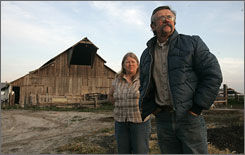 Joe and Janice Pimentel stand near a barn on their dairy near Atwater, Calif. The pair lost the dairy they had owned for 21 years when overwhelming bills forced a foreclosure sale of the property.