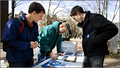 Obama student volunteers Mike Stratta, left, and Christo Logan, right, assist University of Pennsylvania worker Dave Munson as fills out a voter registration form on the university campus in Philadelphia on March 20.