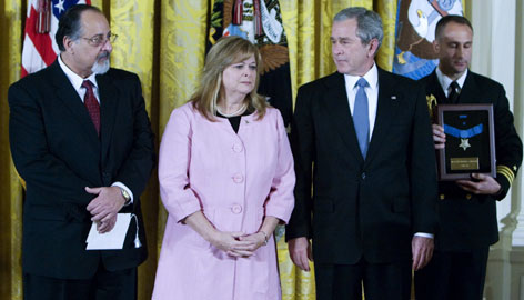 President Bush presents the Medal of Honor to the parents of Petty Officer Second Class Michael Monsoor. George Monsoor, left, and Sally Monsoor, second left, attended the ceremony Tuesday in the East Room of the White House in Washington.