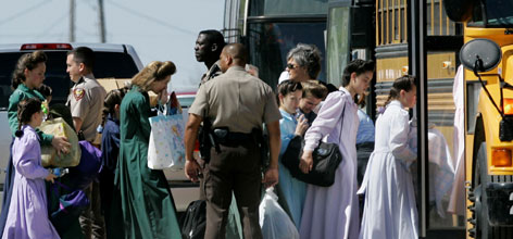 Officers escort members of a polygamist sect onto a school bus in Eldorado, Texas, Sunday. Authorities have removed hundreds of women and children since they received a search warrant to enter the compound Friday.
