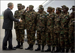 President Bush shakes hands with Rwandan peacekeepers recently returned from the Darfur region of Sudan before his departure on Air Force One at Kigali International Airport in Kigali on Feb. 19.