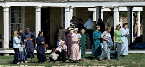 Members of the Fundamentalist Church of Jesus Christ of Latter Day Saints, walk along the grounds of their temporary housing, Fort Concho National Historic Landmark, in San Angelo, Texas, Monday.