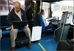 Tim Harrington reads the news and checks email while riding the King's Island Express bus to work on Monday morning.