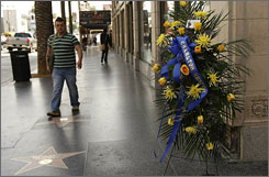 A man walks by flowers placed in the memory of the actor, near his star on the Hollywood Walk of Fame, in Hollywood, California on April 7. Heston died on April 5 at the age of 84.
