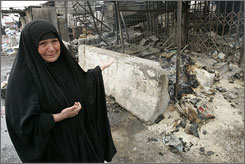 A woman reacts next to destroyed shops after clashes and an airstrike in Baghdad's Sadr City.