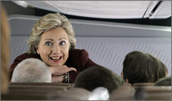 Democratic presidential hopeful Sen. Hillary Rodham Clinton (D-N.Y.) talks as she leans over her seat in her campaign plane at the Indianapolis airport Saturday.