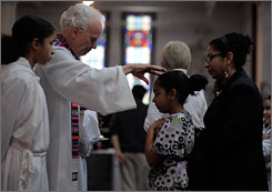 Rev. David Gill blesses Ineliz Camposas her mother, Maribel Campos, waits for Communion during the Spanish Mass at St. Mary of the Angels church in Roxbury, Mass. In an effort to save money, the Boston archdiocese has tried twice to close the parish in an impoverished and high-crime area. 
