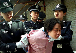 A woman prisoner is taken away in April 2001 for her execution after being sentenced to death at a rally in Beijing.