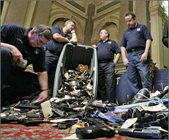 "Philadelphia police officers examine handguns after a news conference held by Rep. Chaka Fattah, D-Pa., regarding the ""Groceries for Guns Exchange"" program Thursday, May 3, 2007, in Philadelphia."