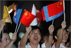 Chinese men and women wave national and Olympic flags as they welcome the arrival of a plane carrying the Olympic flame at a military airport in Bangkok, on Friday, Thailand time.