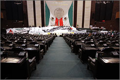 The empty, main room of Mexico's National Congress and its podium. covered with protest banners, in Mexico City on Monday.