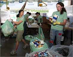Volunteers in Seattle sort through all the trash from a Green Festival event, looking for various recyclable items.