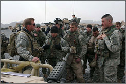 NATO soldiers are briefed by a U.S. Special Forces soldier, left, before they leave for a patrol in Spawan Ghar, Panjwayi Province, Afghanistan, on Jan. 18.
