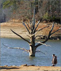 Fisherman Rick Johnson walks along Lake Lanier in Gainesville, Ga. in Dec. 2007. Hefty water bills have followed the record drought, with Atlanta's water utility seeking a 15% rate increase to offset conservation losses.