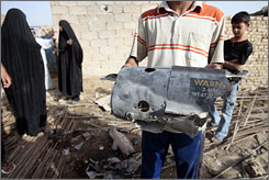 An Iraqi man holds the remains of a U.S. bomb dropped during an overnight airstrike on a neighborhood of Baghdad's Sadr City on Tuesday.
