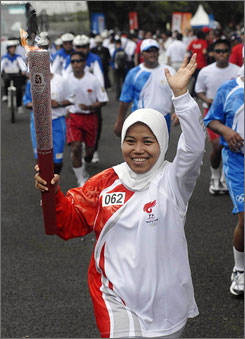 Environmental activist Tri Mumpuni runs with the Olympic torch during the Beijing Olympic torch relay in Jakarta, indonesia, Tuesday.