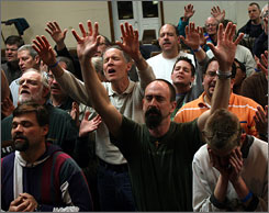 Members of the Men's Ministry of the Assemblies of God Denomination raise their hands in worship at the Spencer Lake Bible Camp in Waupace, Wis., on March 7. Conservative Protestants, such as the Assemblies of God and Nazarene and Pentecostal churches are less likely to hold onto wealth, a sociologist says.