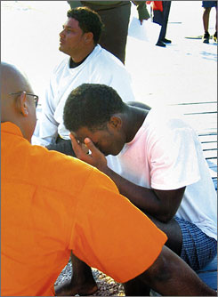 A Haitian migrant, right, who survived the capsizing of a boat off Nassau, Bahamas, is questioned by a Bahamian official at the Nassau Harbour Patrol Unit on Sunday. The migrant is one of three who survived the tragedy.