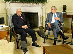 President Bush, right, and Mahmoud Abbas, president of the Palestinian Authority, left, answer questions from the media during their meeting in the Oval Office of the White House on Thursday.