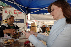 """After learning her job would be cut, Kelly Daly started reaching for sugar. At the Bowling Green Farmers Market in New York, she purchases chocolate-dipped macaroons and a """"chocolate explosion"""" cookie package from Johnny Amaro at Meredith's Bread Muffin & Pies."""