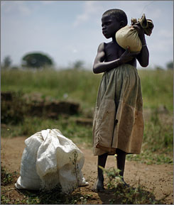 Eunice Ayugi, 9, holds a cloth filled with kernels of beans she picked that were dispersed on the ground after an air drop in the Olilim camp for internally displaced people in the Lira District of Northern Uganda in October.