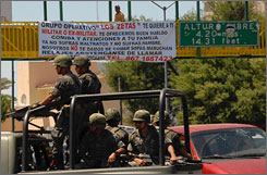 "A truck carrying Mexican army soldiers drives past a pedestrian bridge holding a giant banner signed by the Zetas, the enforcement arm of the Gulf drug cartel, in the border city of Nuevo Laredo, northern Mexico, on April 13. The banner reads, in Spanish: ""Operative group 'The Zetas' wants you, soldier or ex-soldier. We offer a good salary, food and benefits for your family. Don't suffer anymore mistreatment and don't go hungry. We wont give you instant noodle soup."""